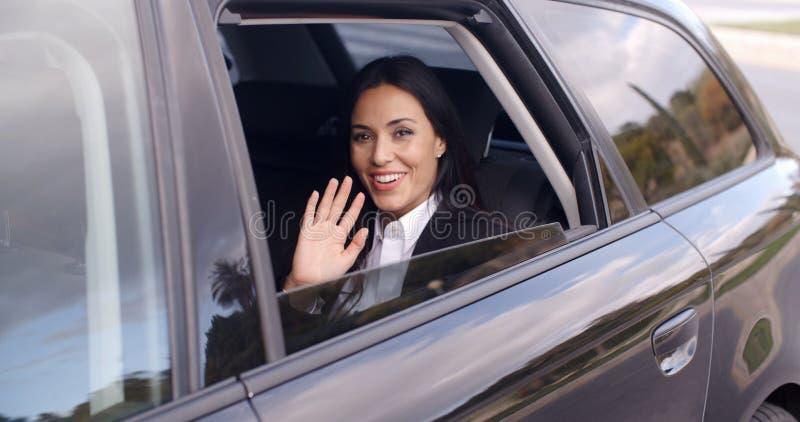 Femme mignonne d'affaires s'asseyant dans la main de ondulation de voiture photographie stock