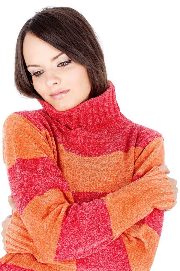 Femme mignonne de brunette dans un chandail rouge-orange de laines image libre de droits