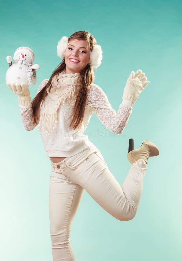 Femme mignonne de sourire avec le petit bonhomme de neige L'hiver photo stock