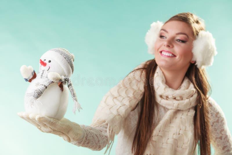 Femme mignonne de sourire avec le petit bonhomme de neige L'hiver photos libres de droits
