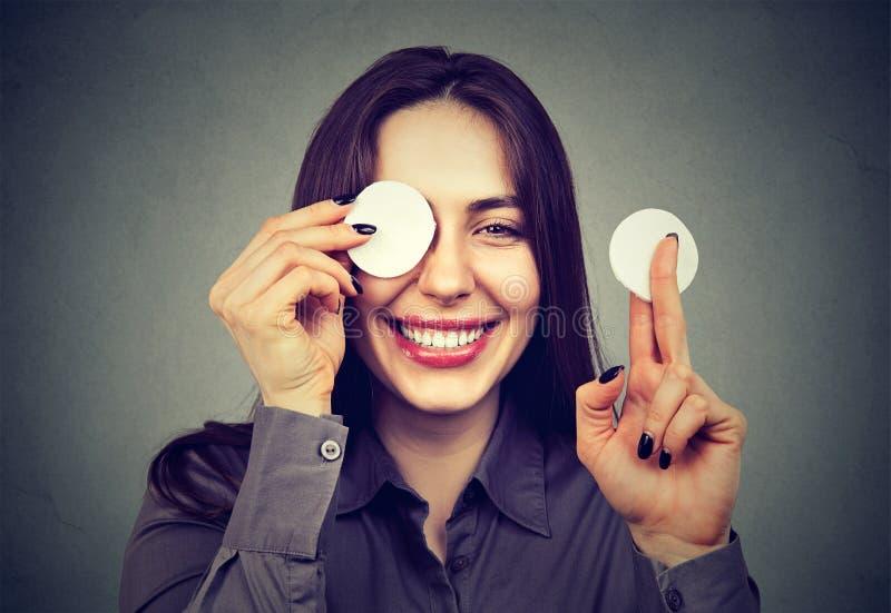Femme mignonne enlevant le maquillage appliqué avec une protection d'éponge de coton photo stock