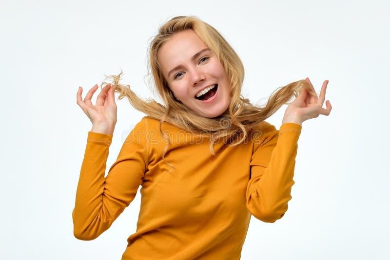 Femme mignonne et avec du charme jouant avec ses longs cheveux, souriant à la caméra photographie stock