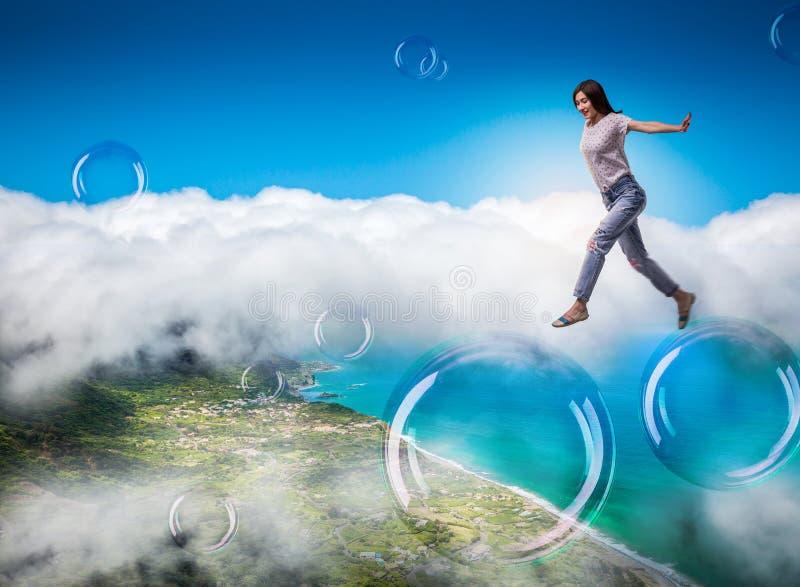 Femme mignonne sautant dans le ciel sur de grandes bulles de savon image libre de droits