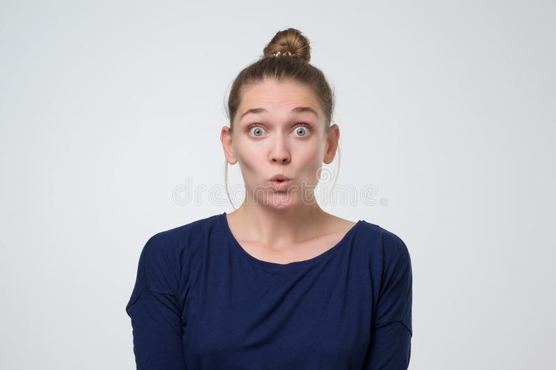 Femme mignonne stupéfaite de caucasain, regardant fixement avec les yeux sautés la caméra images libres de droits