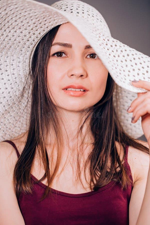 Femme mignonne très belle dans le chapeau rayé sur le fond gris regardant l'appareil-photo Été, plage, le soleil photo stock