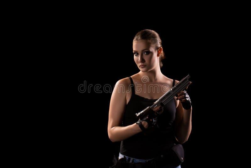Femme militaire avec une arme à feu au-dessus de fond noir images libres de droits