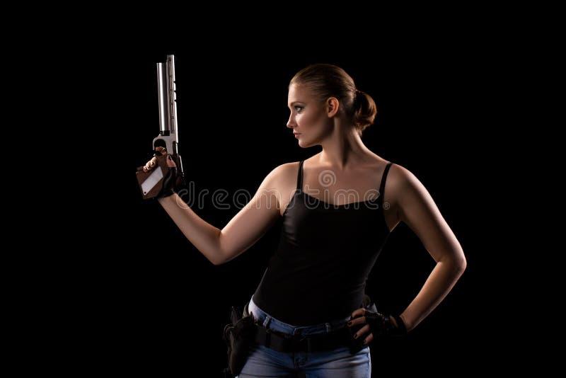 Femme militaire avec une arme à feu au-dessus de fond noir photos libres de droits