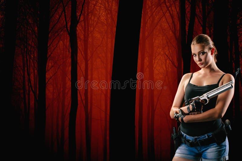 Femme militaire avec une arme à feu au-dessus de fond noir photo stock