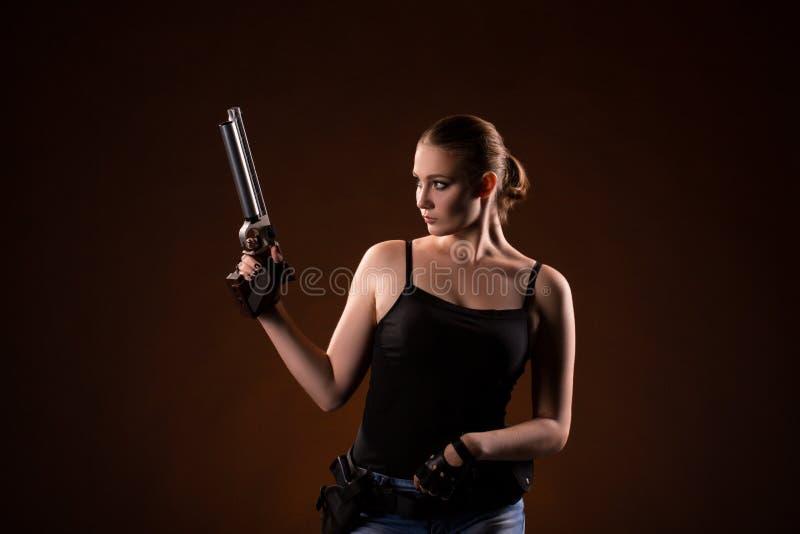Femme militaire avec une arme à feu au-dessus de fond noir photographie stock