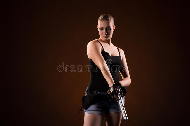 Femme militaire avec une arme à feu au-dessus de fond noir photographie stock libre de droits