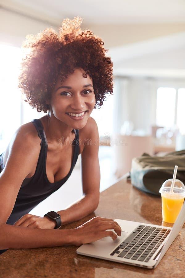 Femme millénaire d'Afro-américain vérifiant des données de forme physique sur l'ordinateur portable souriant à la caméra, vertica photos libres de droits