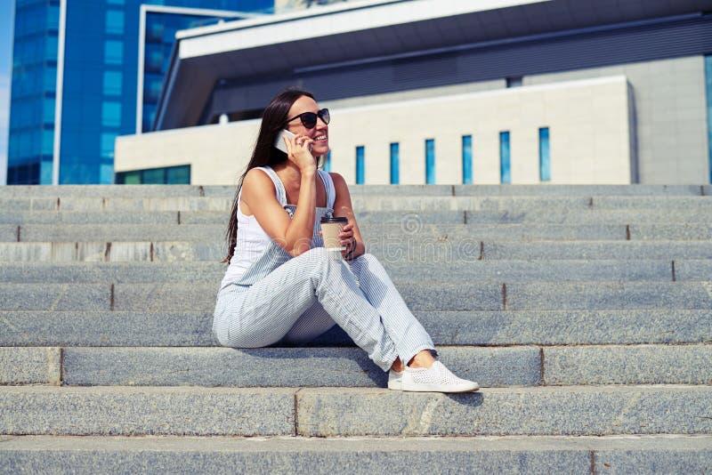 Femme mince dans des combinaisons détendant le café potable et parlant dessus photos libres de droits