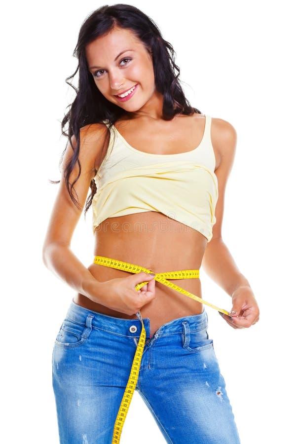Femme mince dans des jeans avec la mesure de bande images stock