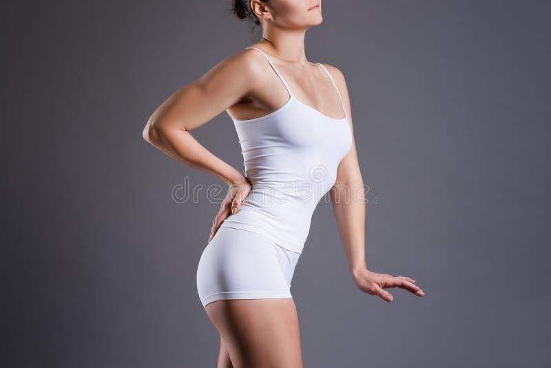 Femme mince dans les sous-vêtements blancs sur le fond gris de studio, corps féminin parfait image libre de droits