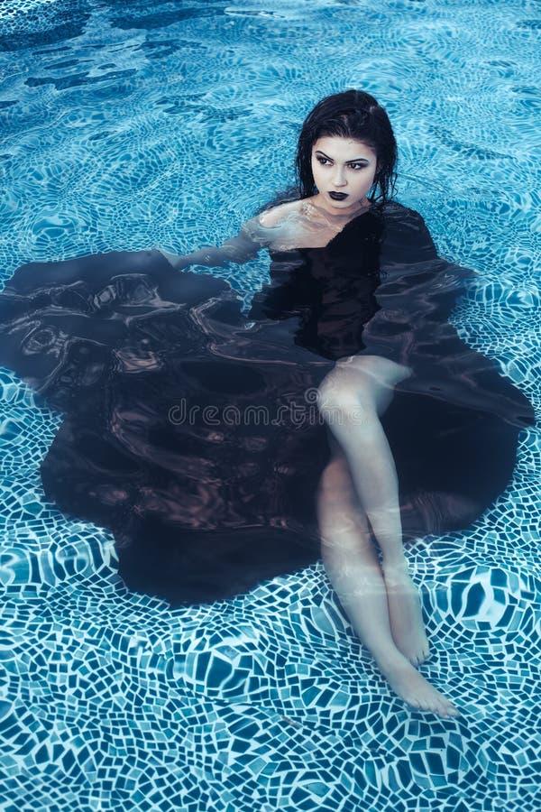 Femme mince sexy dans la piscine dehors photos stock
