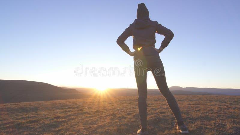 Femme mince sportive à un lever de soleil pulsant dans les montagnes photo stock