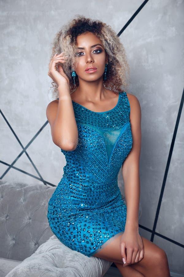 Femme modèle afro-américaine de haute couture dans les ldress lumineux bleus posant dans le studio, portrait de belle fille avec  photographie stock libre de droits