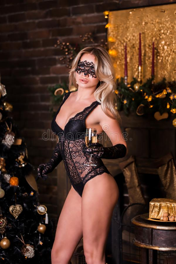 Femme modèle avec le verre du masque vénitien de port de mascarade de champagne à la partie, champagne potable au-dessus de rouge image libre de droits