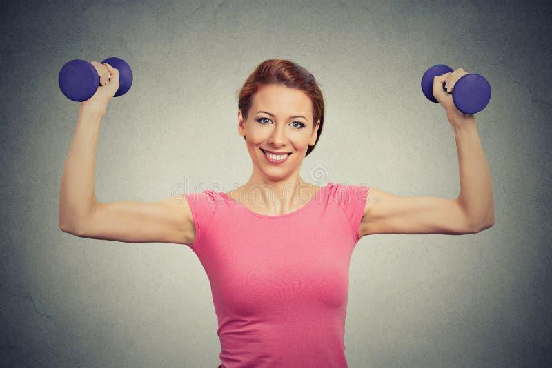Femme modèle en bonne santé convenable fléchissant des muscles soulevant des haltères images libres de droits