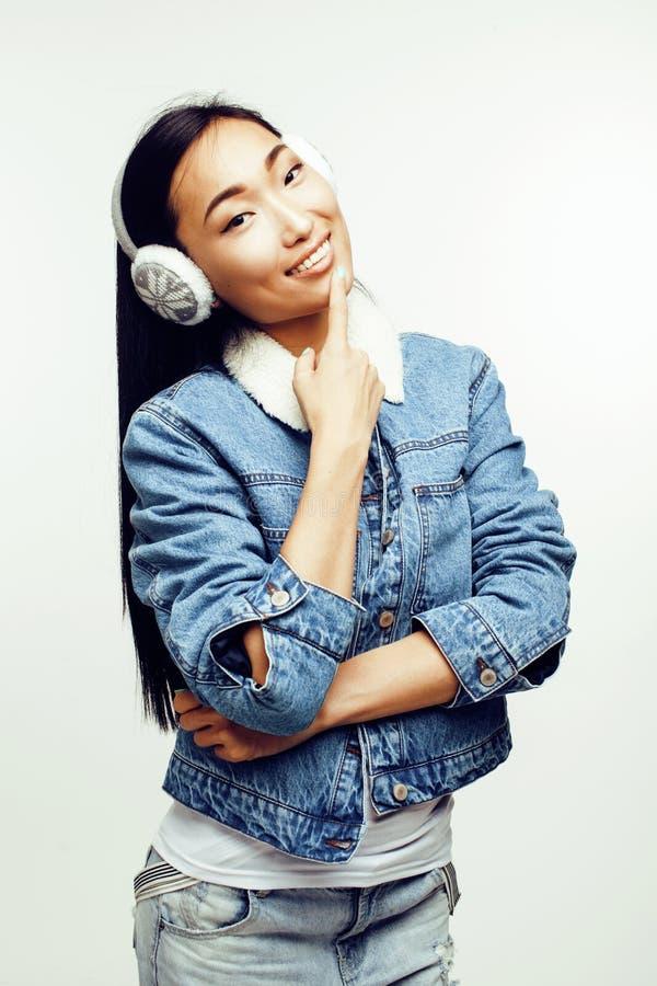 Femme moderne assez asiatique de hister de mode de jeunes dans des écouteurs d'hiver posant émotif gai d'isolement sur le blanc photographie stock