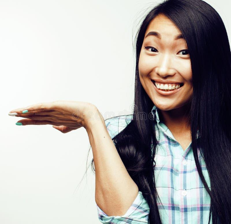 Femme moderne assez asiatique de hister de mode de jeunes dans des écouteurs d'hiver posant émotif gai d'isolement sur le blanc photographie stock libre de droits