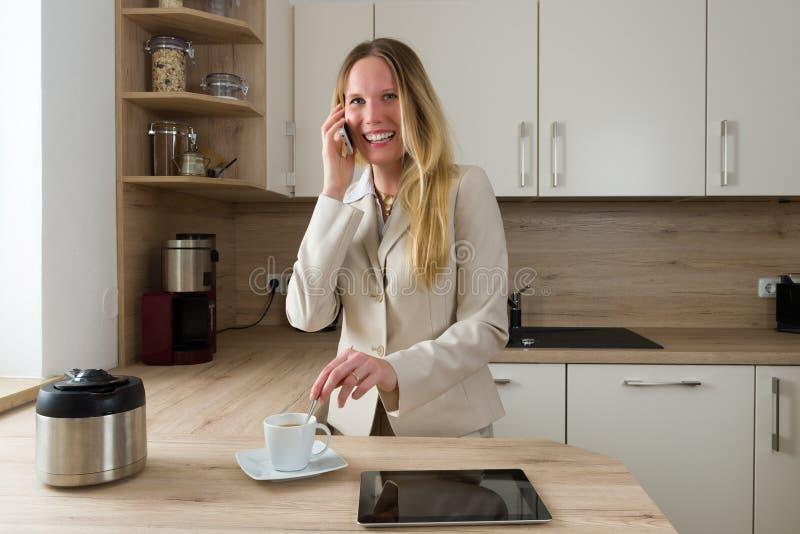 Femme moderne d'affaires avec le smartphone et le café dans la cuisine images libres de droits
