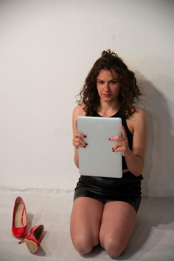 Femme moderne de jeune brune bouclée se mettant à genoux contre un mur blanc image stock