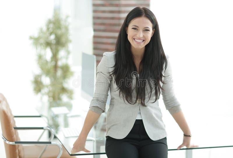 Femme moderne de sourire d'affaires se tenant près d'une table de travail photos stock