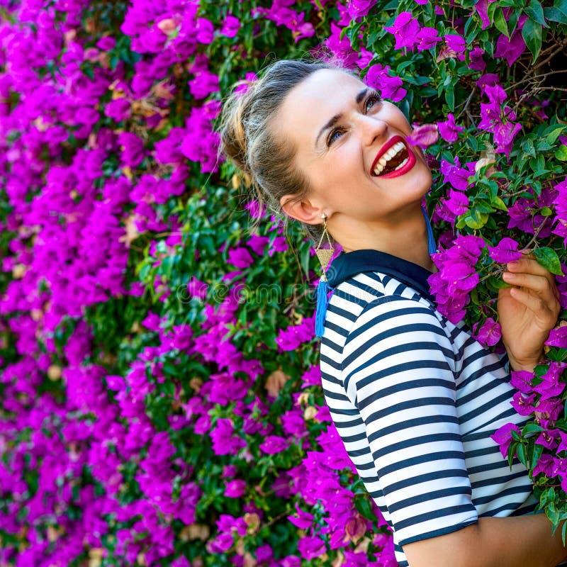 Femme moderne gaie près de lit de fleurs magenta coloré image stock