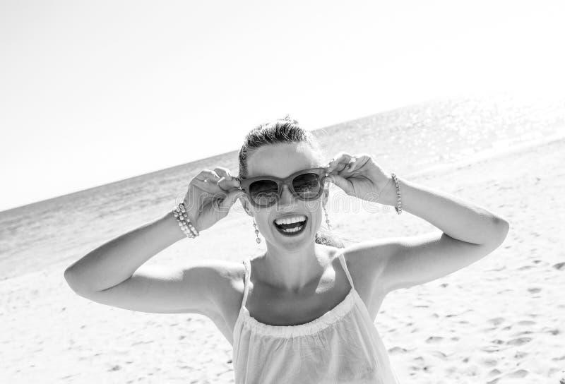 Femme moderne heureuse sur le bord de la mer tenant des lunettes de soleil image stock
