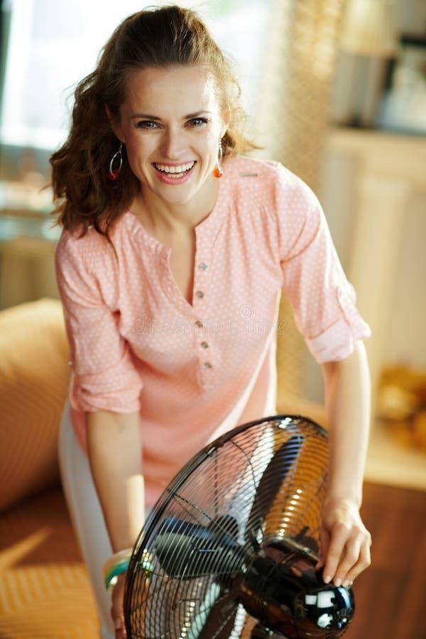 Femme moderne heureuse swtitching sur la fan m?tallique de position de plancher photos libres de droits