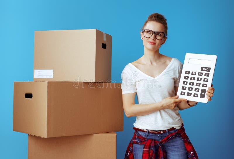 Femme moderne songeuse près de boîte en carton avec la calculatrice sur le bleu photos libres de droits
