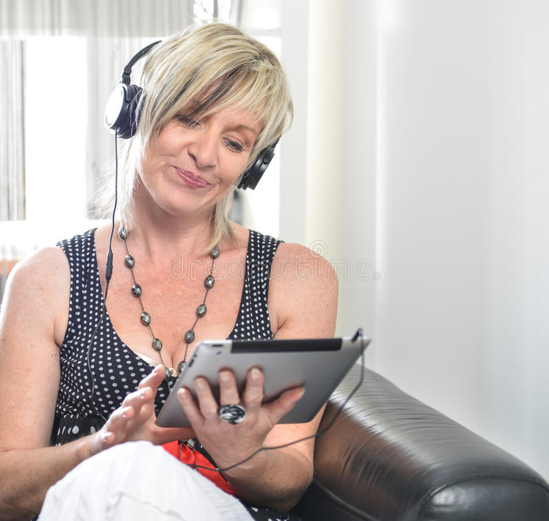 Femme moderne supérieure s'étendant dans le sofa avec le comprimé et l'Au électroniques photographie stock libre de droits