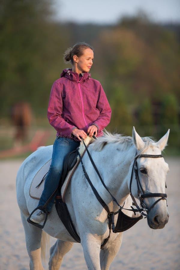 Femme montant un cheval image stock