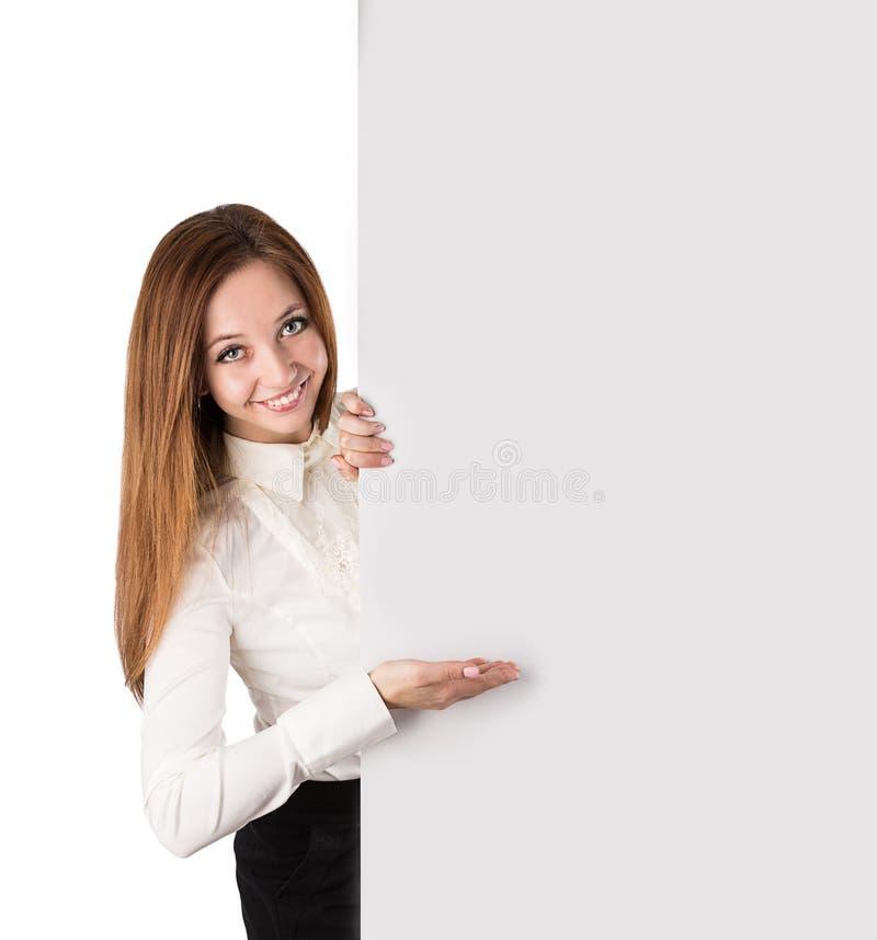 Femme montrant avec la main sur le conseil blanc photo stock