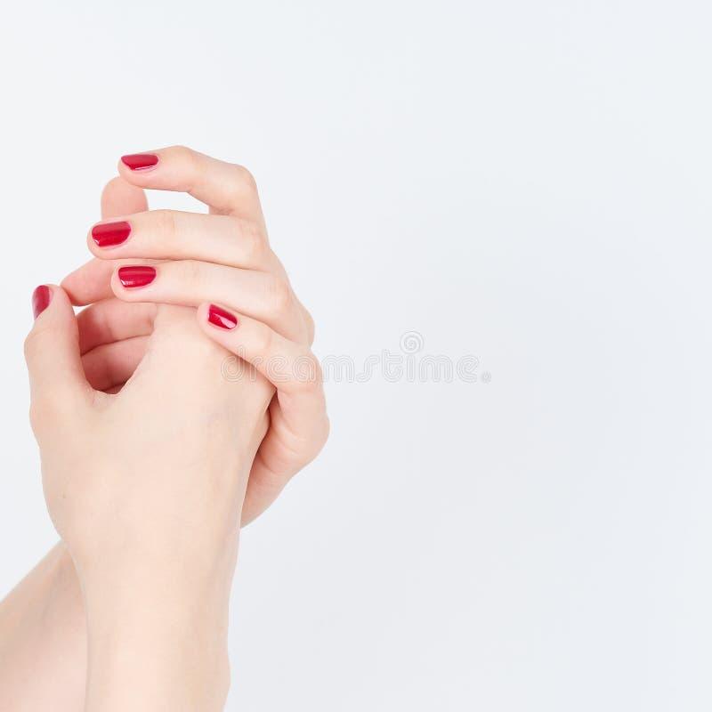 Femme montrant des mains de manucures avec le vernis à ongles rouge sur l'espace blanc de copie de fond image stock