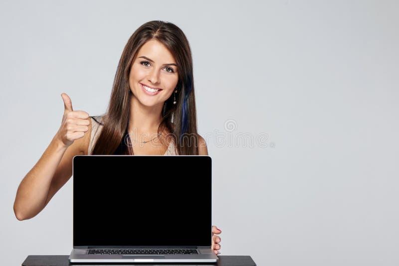 Femme montrant l'écran noir vide d'ordinateur portable photos stock