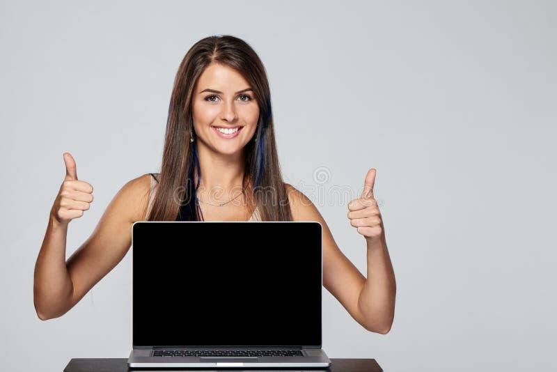 Femme montrant l'écran noir vide d'ordinateur portable photographie stock libre de droits