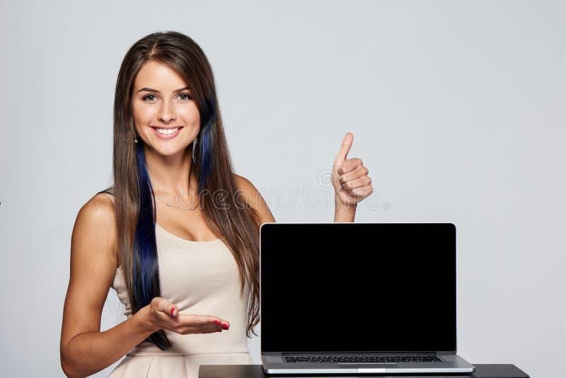 Femme montrant l'écran noir vide d'ordinateur portable photo stock