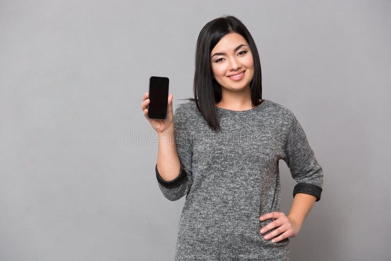 Femme montrant l'écran vide de smartphone image stock