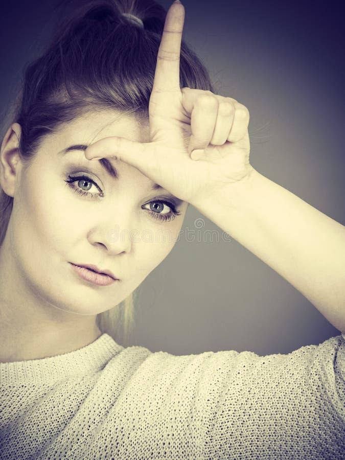 Femme montrant le geste de perdant avec L sur le front image stock