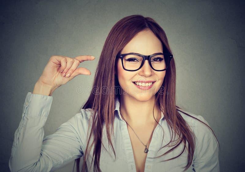 Femme montrant le geste de taille d'un peu avec des doigts de main image libre de droits
