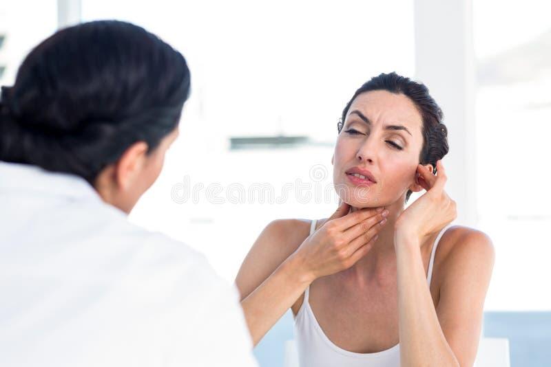 Femme montrant sa gorge à son docteur photos stock