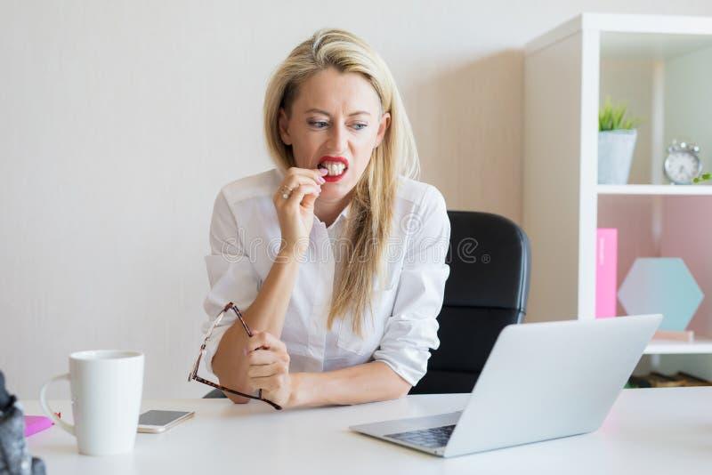 Femme mordant ses ongles dans le bureau photographie stock