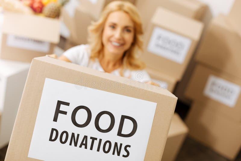 Femme motivée sincère distribuant la nourriture gratuite photos libres de droits