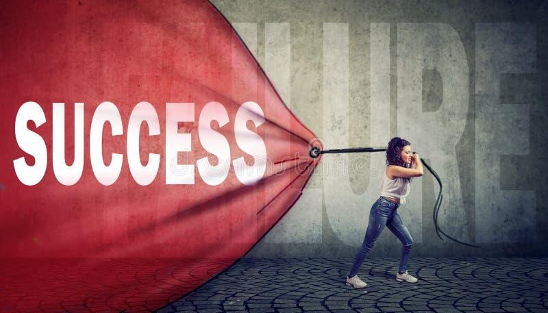 Femme motivée tirant une bannière rouge avec le mot de succès surmontant un échec photos stock