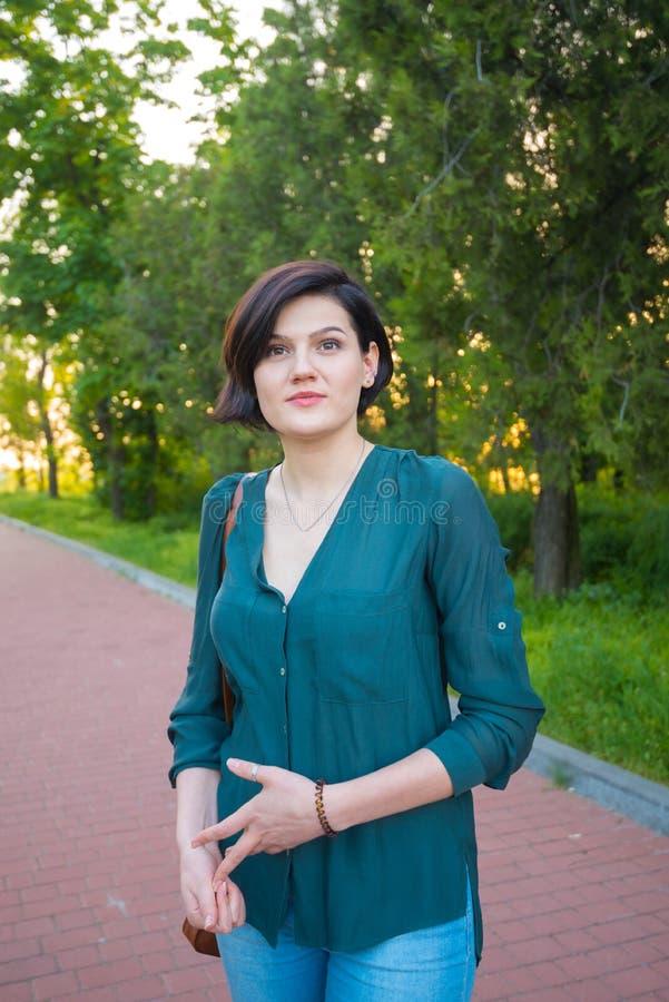 Femme multiraciale moderne pendant une promenade en parc de ville photo stock