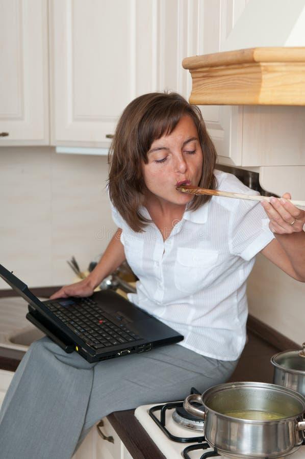 Femme multitâche - cuisson du repas et fonctionner photo libre de droits