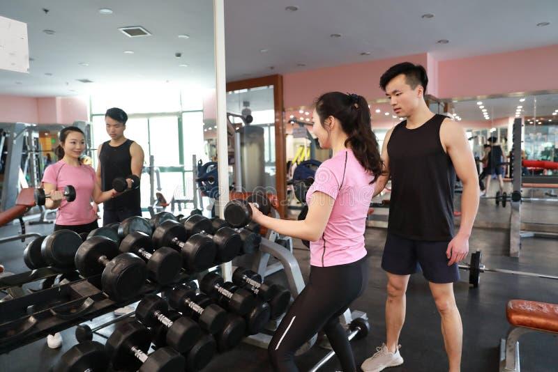 Femme musculaire établissant dans le gymnase faisant des exercices avec des haltères aux biceps, ABS nu masculin fort de torse photo stock