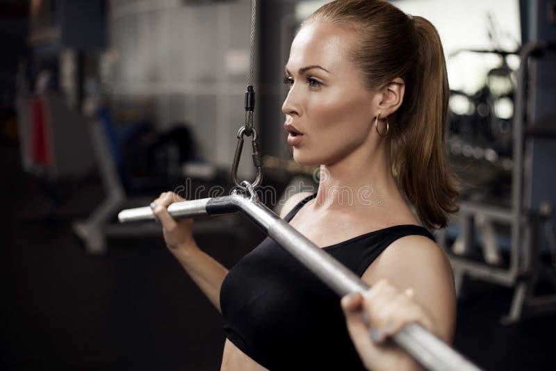 Femme musculaire d'ajustement exerçant des muscles de bâtiment image stock